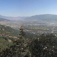 View from the north ridge with Jade Dragon Snow Mountain at left, the city of Lijiang and Elephant Hill at far right